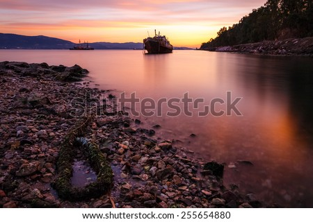 Old abandoned shipwreck near Aspropirgos, Greece against a colorful sky, long exposure photograph - stock photo