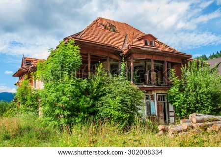 Old abandoned stone house with a leaky roof tiles in the Carpathians. Green vegetation and hills around - stock photo