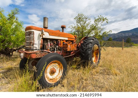 Old abandoned tractor in grass field