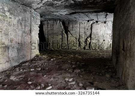 Old abandoned tunnel in the underground quarries. Entrance to the catacombs of Odessa, Ukraine. As a creative background for design formulation dark - stock photo