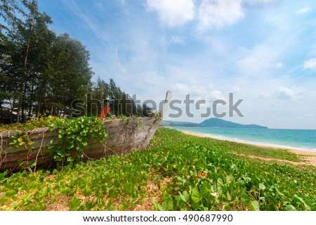 Old abandoned wooden boat wreck on deserted tropical beach
