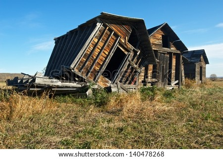 old abandoned wooden granaries the closest one falling of it's support due to the wind - stock photo