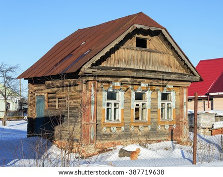 Old abandoned wooden house with rusty metal roof in the village, sunny winter day