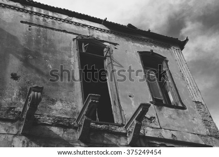 Old abandoned wrecked house. Time concept. Toned dark black and white photo. - stock photo