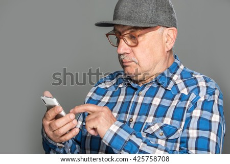 Old active man using mobile phone isolated on grey background - stock photo