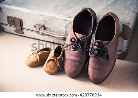 Old adult leather shoes and kid shoes with old suitcase, Travel together or father's day concept