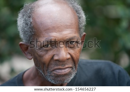 Old african american homeless man outdoors with sad eyes.