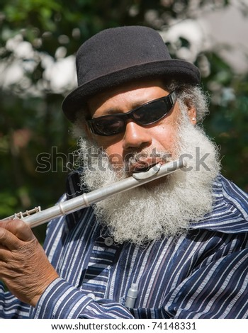 Old African American musician playing flute outdoors - stock photo