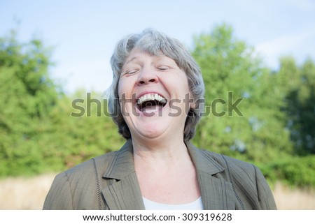 Old age woman laughing out loud - stock photo