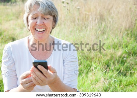 Old age woman using smart phone - stock photo