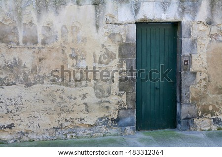 Old aged building made of white and beige stone masonry with green wooden door. Brittany. France.