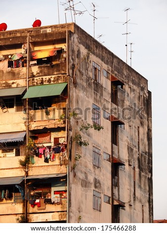 old aged dirty facade of an old residential building in downtown Bangkok with clothes hanging on the windows  - stock photo
