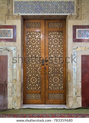 Old aged wooden closed door decorated with arabesque ornaments, Old Cairo, Egypt