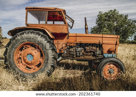 old agricultural tractor abandoned in a farm field - stock photo