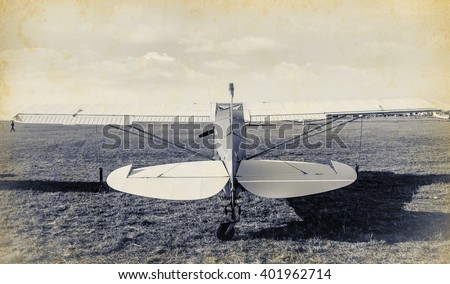 Old airplane at the airfield, back side view. Air concept of retro aviation. Vintage image of old aircraft. Wings, tail and fuselage of the airplane on airfield, rear view. - stock photo