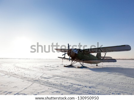 Old airplane parked on little north snowy airfield - stock photo