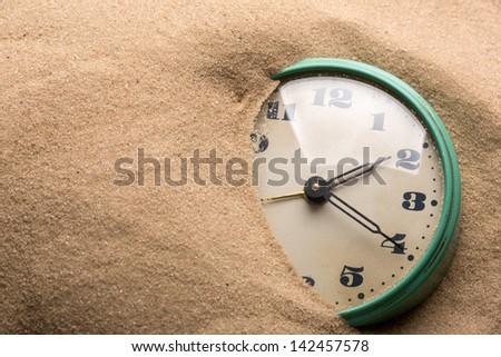 Old alarm clock in sand - stock photo