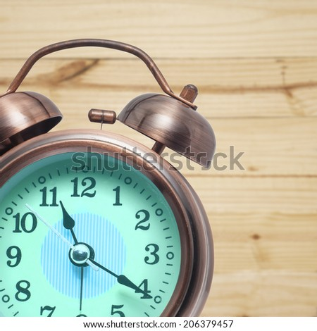 Old alarm clock isolated on Wood background