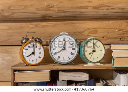 Old alarm clock on a shelf with books - stock photo