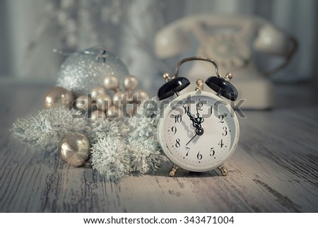 Old alarm clock showing five to midnight and white vintage phone. Happy New Year 2016! This image is toned. - stock photo