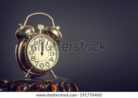 Old alarm clock showing twelve o'clock over dark background. - stock photo