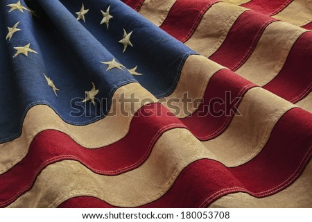 Old American flag designed during the American Revolutionary War features 13 stars to represent the original 13 colonies. According to the legend the original Betsy Ross flag was made on July 4, 1776. - stock photo