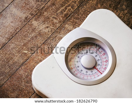 Old analog weight scale on wood floor - stock photo