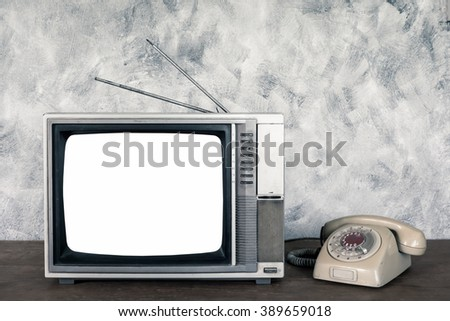 Old analogue television and telephone on wood table with textured background. - stock photo