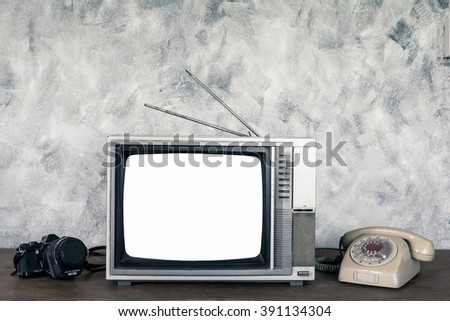 Old analogue television,old telephone and camera on wood table with textured background. - stock photo