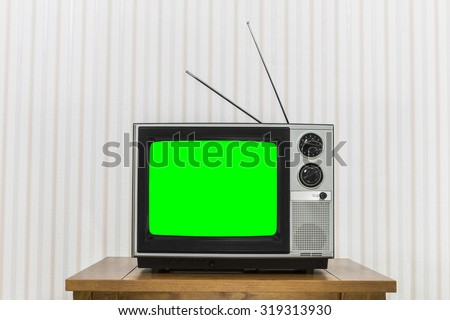 Old analogue television on wood table with chroma key green screen. - stock photo
