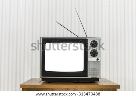 Old analogue television on wood table with white cut out screen.