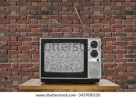 Old analogue television with static screen and brick wall. - stock photo