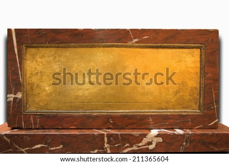 Old ancient brass yellow metal or gold plate framed and nailed on brown marble stone wall on white background. Clipping path included - stock photo