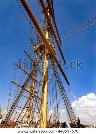Old Ancient sailboat. Historic three-masted sailing ship without sails docked in harbor waterfront. Shaded view of fragment of a sailing schooner, as background for creative design of tourist posters - stock photo