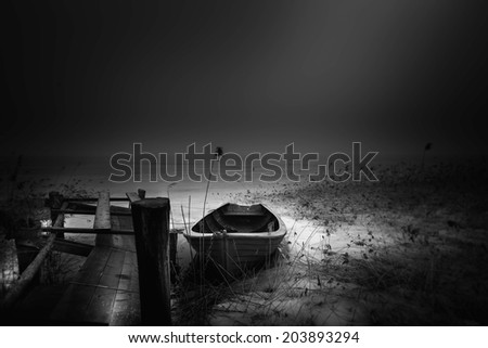 Old and abandoned boat in the morning mist - stock photo