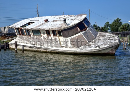 Old and abandoned derelict wooden passenger boat with damaged hull tied at dock half sinking in water after a hurricane - stock photo