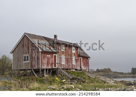 Old and abandoned is this idyllic red wooden house on the outskirts of henningsvaer - stock photo
