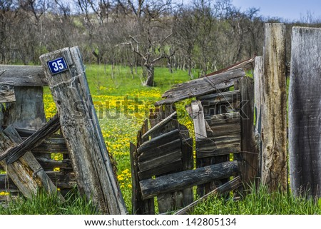 Old and broken gate in front of a garden/Spring behind the gate/ - stock photo
