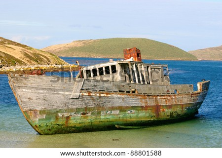 Old and broken wooden boat stranded on the sandy beach - stock photo