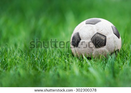 Old and classic Soccer ball or football ball on green field - stock photo