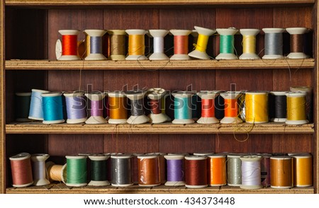Old and colorful thread spools on wooden shelf. - stock photo