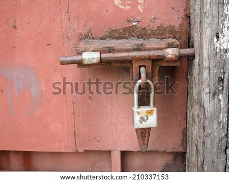 old and corroded padlock on steel door
