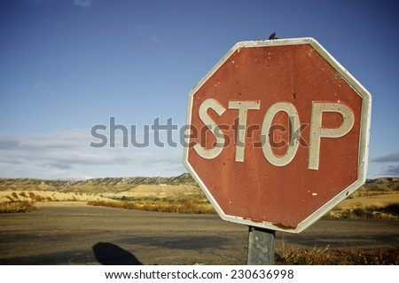 old and damaged stop sign against a blue sky - stock photo