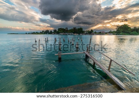 Old and damaged wooden jetty on lake Poso in central Sulawesi, Indonesia, with dramatic cloudscape at the horizon at sunset. - stock photo
