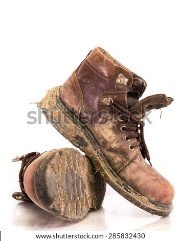 Old and Dirty boots in mud. on white background - stock photo