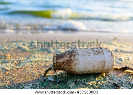 Old and Dirty Plastic Bottle on the beach with water pollution background (green algae bloom) - stock photo