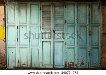 Old and dirty vintage style wooden door, antique wall - stock photo
