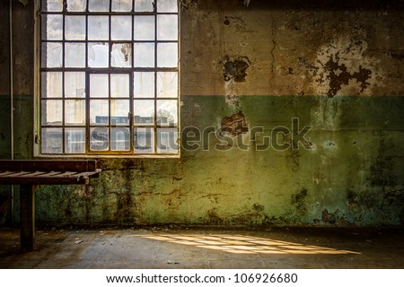 Old and dirty wall of the interior of an out of order factory - stock photo