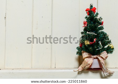 Old and dust christmas tree with decoration and wooden wall. - stock photo