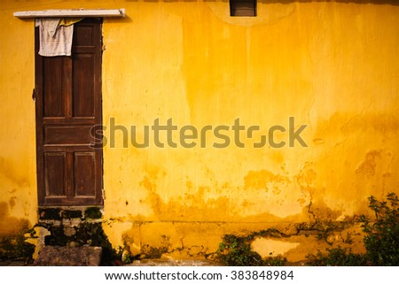 Old and grungy yellow wall with wooden door - stock photo